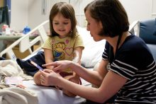Elizabeth Griffin, MD '08, a pediatrics resident, shows 5-year-old Juliana Sweet a stack of physician trading cards. Griffin created the cards as a way to help patients and their families become familiar with the people who care for them throughout the day. Photo by Jesse S. Jones