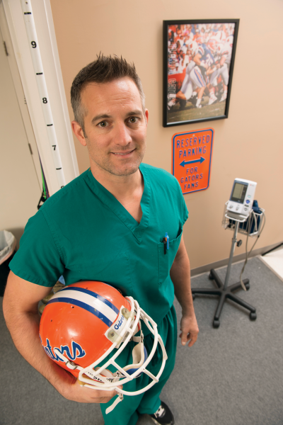 Michael Gilmore, MD '99, poses in scrubs and holds a Gator helmet.